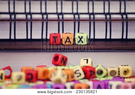 Financial And Tax Concept Cubes With Word Tax On Diary.