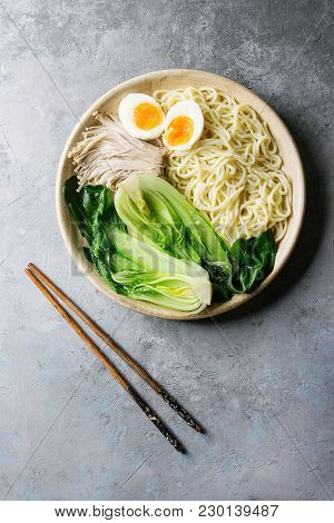 Asian Dish Udon Noodles With Boiled Egg, Mushrooms, Boc Choy Served In Ceramic Bowl With Chopsticks