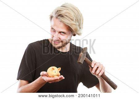 Money, Savings, Finances Concept. Young Blonde Man Wearing Black T Shirt Trying To Break Piggy Bank