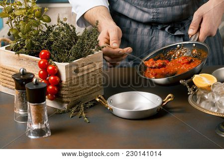 Chef Spreading Tomato Sauce From Frying Pan At The Kitchen. Gourmet Restaurant