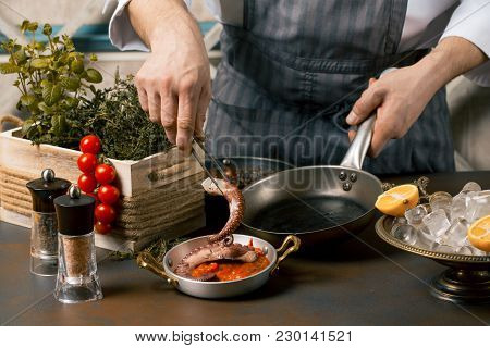 Chef Cooks Spreadsheets Octopus Tentacles. Chef Lays Octopus From The Frying Pan On Tomato Sauce. Go
