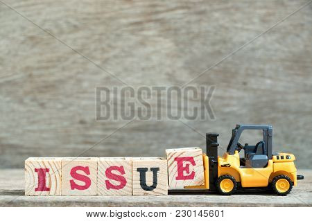 Toy Forklift Hold Letter Block E To Complete Word Issue On Wood Background