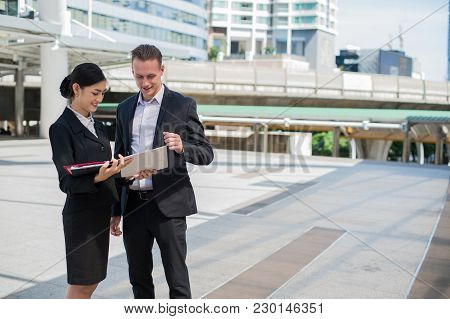 Asian Businesswoman And Caucasian Businessman Discussion Business Issue From Financial Report On Pap