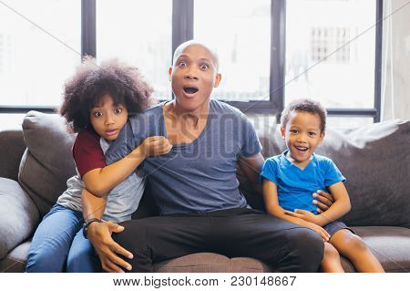 Whole Family Of African American Watching And Staring Horror Movie On Tv At Home. They Are Getting F