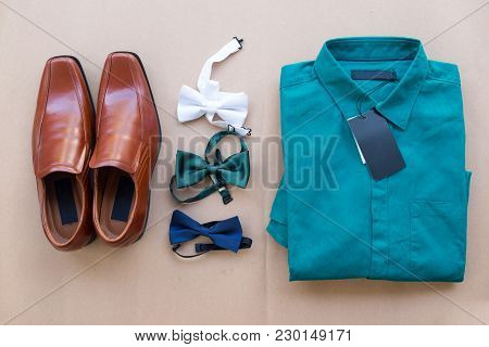 Flat Lay Of Men Casual Fashion Outfits On Brown Background (brown Shoes, Green Shirt And Various Bow