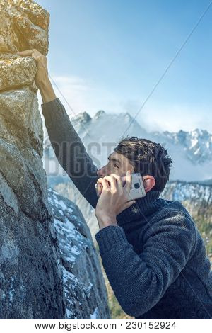 A Young Man Climbs The Mountain To The Top And Talking Holding The Phone. Concept Of Persistence And
