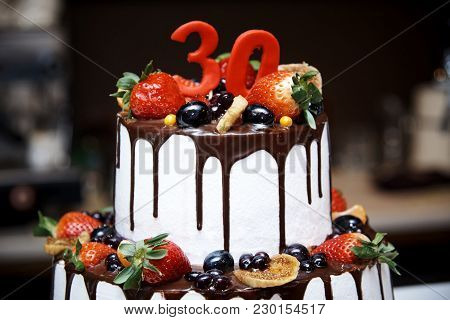 Two-tiered White Cake With Fresh Fruits And Chocolate Decorated With A Figure Of Thirty Close-ups.