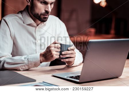 Difficult Task. Thoughtful Responsible Unshaken Employee Looking At The Screen Of His Laptop Holding