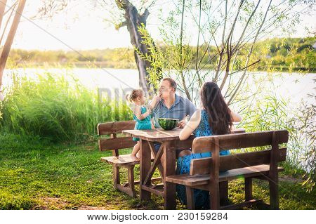Family In Summer On A Picnic Near A Pond, Water. Family Holiday In Nature. A Little Daughter Feeds H