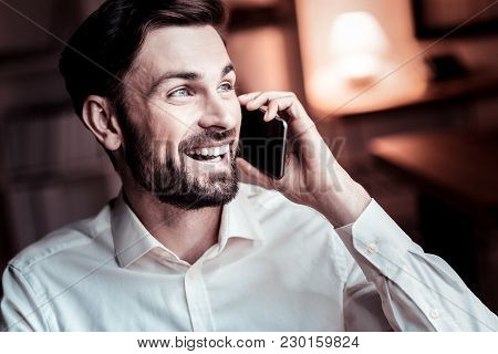 Nice To Hear You. Happy Pleasant Stylish Man Spending Time In The Specious Room Smiling And Having P