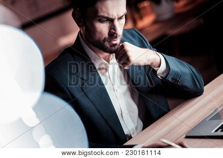 Business Will Not Wait. Serious Occupied Stylish Employee Sitting By The Table Near The Laptop Holdi