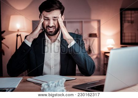 Unexpected Pain. Ill Unshaken Stylish Man Sitting In The Office Holding Hands Near Head And Having H