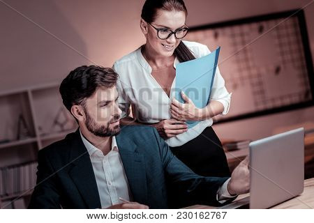 Good Results. Satisfied Pretty Bespectacled Woman Standing Near Her Colleague Looking At The Laptop