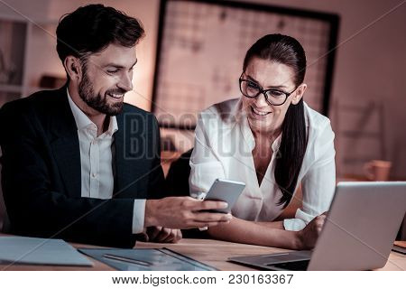 I Will Show You. Satisfied Beardful Pleasant Man Sitting In The Cabinet Near A Woman Smiling And Sho
