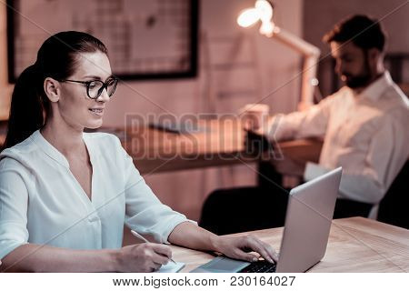 Its My Task. Concentrated Reliable Cute Colleague Sitting By The Table Near Her Partner Making Notes