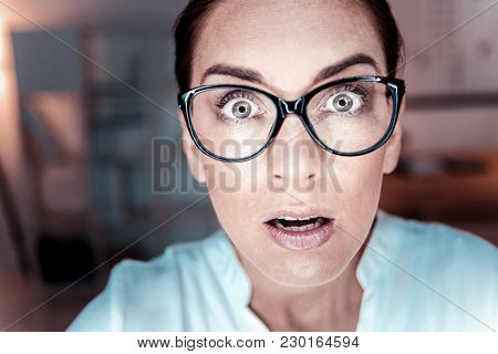 Its Unbelievable. Amazed Bespectacled Surprised Woman Being In The Empty Room Looking Having Astonis