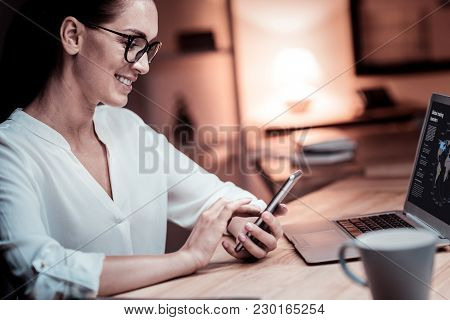 New Message. Joyful Pretty Bespectacled Woman Sitting In The Office Opposite The Laptop Holding Her