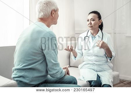Some Advices. Cute Experienced Pleasant Nurse Sitting Near The Man In The Room Speaking And Giving A