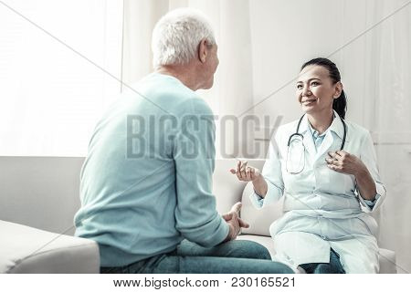 Family Doctor. Pleasant Joyful Skilled Doctor Looking At The Patient Talking To Him And Gesticulatin