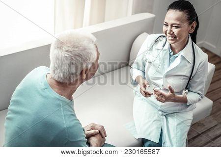 Regular Meeting. Joyful Pretty Pleasant Nurse Sitting In The Room On The Sofa Opposite To Her Patien