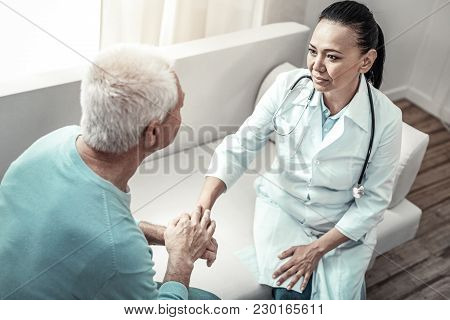 Take It Easy. Cute Experienced Concentrated Nurse Sitting In The Room In Front Of Her Patient Calmin