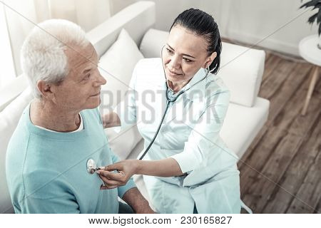 Its Alright. Cute Experienced Pleasant Nurse Sitting In The Room On The Sofa Examining Her Patient A