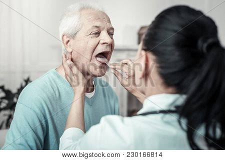 Illness Again. Gray Haired Serious Aged Man Having Medical Examination Sitting Opposite The Nurse An