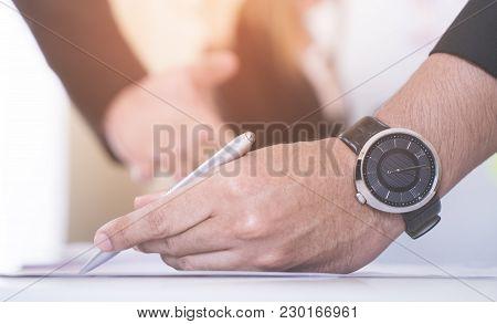 Business Man Marking On Data Sheet Using Metal Pen