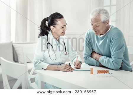 New Recommendations. Mature Pretty Pleasant Nurse Sitting In The Room By The Table With Her Patient