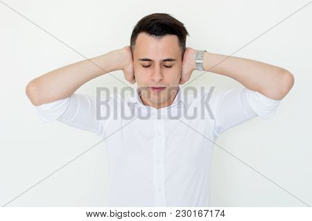 Closeup Portrait Of Serious Handsome Young Business Man Covering Ears With Hands With His Eyes Close