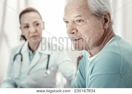 Think About It. Agitated Serious Aged Man Sitting By The Table Looking Aside And Concentrating On Hi