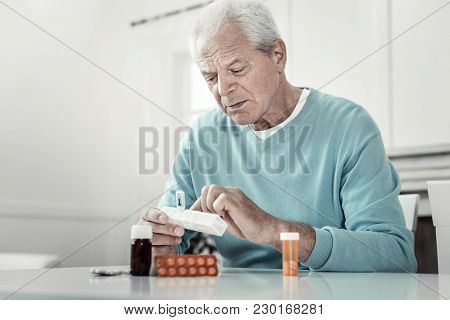 It Will Helps. Concentrated Senior Serious Man Sitting By The Table Holding Pack Of Tablets And Focu