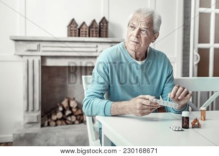Its Better For Me. Thoughtful Serious Gray Haired Man Sitting By The Table In The Bright Room Lookin