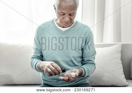 Doctors Advice. Serious Pleasant Aged Man Sitting In The Room On The Sofa Near The Window Pouring Pi