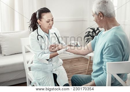 Prepare For This. Calm Serious Confident Nurse Sitting On The Chair Holding Patients Arm And Making