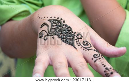 Henna Tattoo On A Hand And Finger, Floral Motif Drawing. Henna Being Applied To Hand, Freshly Applie