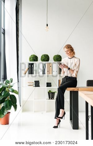 Image of happy young business woman in office looking aside chatting by mobile phone.
