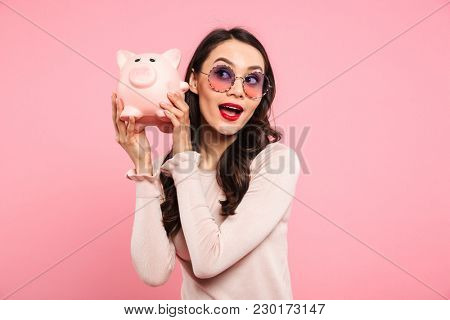 Image of lovely woman 20s with long dark hair in girlish glasses holding piggybank isolated over pink background