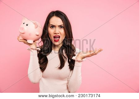 Irritated disappointed woman in casual clothing holding money box and expressing bankruptcy isolated over pink background