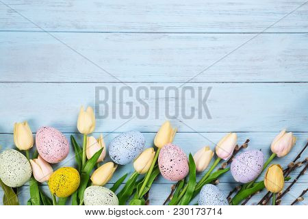 Easter Colorful Eggs With Tulips On Blue Wood Background. Easter Frame Or Post Card With Copy Space,