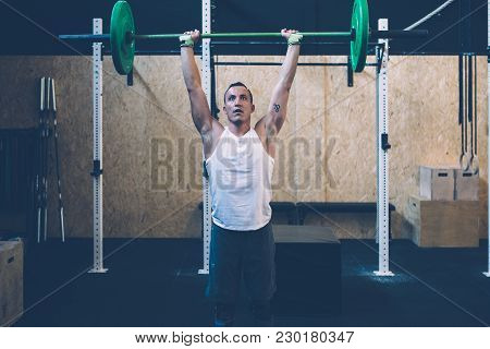Young Athlete Man Doing Thruster Workout With The Barbell Over The Head At The Box Gym