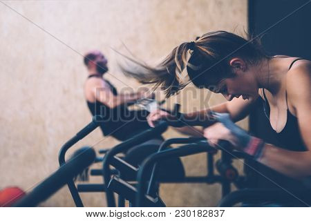 Side View Of A Sporty Girl Doing Calorie Assault Exercise With Her Colleague Doing Glute Ham Develop
