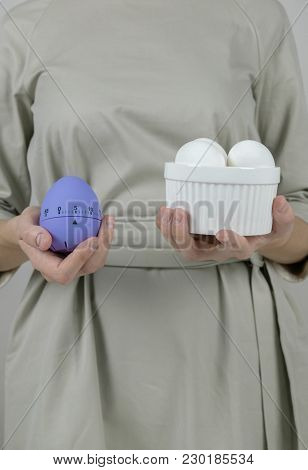 Unrecognizable Woman In Grey Dress Holding White And Violet Kitchen Timer Eggs Preparing For Easter