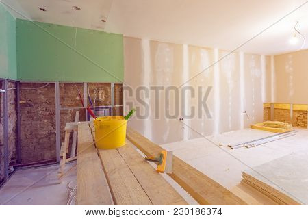 Putty Knife, Yellow Bucket With Glue And Glue Rollers On The Wooden Board In Room  Is Under Construc