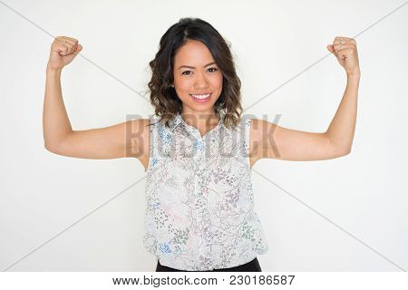 Cheerful Cool Asian Girl Showing Her Power And Looking At Camera. Smiling Young Woman Showing Her Bi