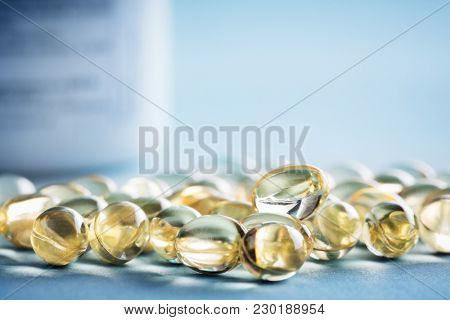 Vitamin D laying on the table with prescription bottle behind them. Supplements pills.