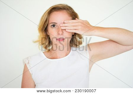 Serious Calm Young Woman Covering One Eye When Testing Vision. Unsmiling Woman Peeking With One Eye.