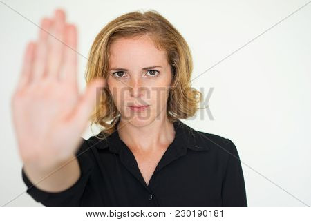 Serious Unsmiling Woman Showing Stop Gesture And Looking At Camera. Displeased Lady Boss Rejecting Y