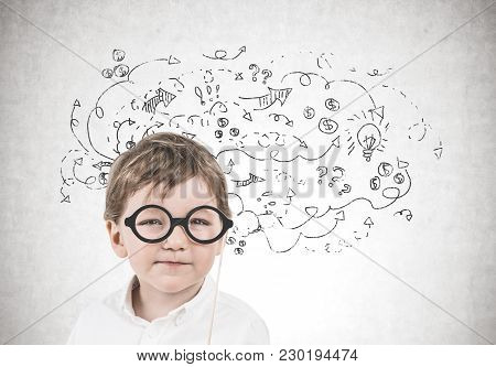 Cute Little Boy In A White Shirt Is Wearing A Pair Of Glasses With A Thick Frame And Thinking While