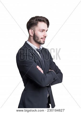 Side View Of A Pensive Young Businessman With A Beard. He Is Wearing A Suit And A Tie And Standing W